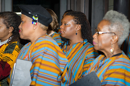Choir members at the vigil stand by as speakers share their thoughts about the life of Nelson Mandela.