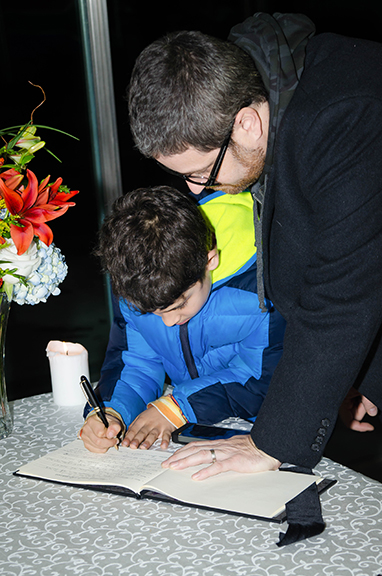 A child writes a message in the condolence book for Nelson Mandela at the South African Embassy.