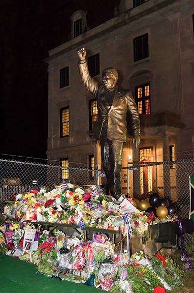 Nelson Mandela mourners left flowers, candles and mementos at the statue of the South African leader outside of the embassy in DC.