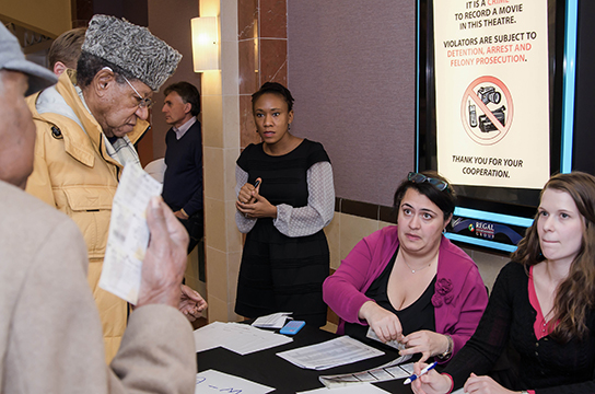 "TransAfrica volunteers check-in attendees to the pre-release screening of ""Mandela: Long Walk to Freedom"""