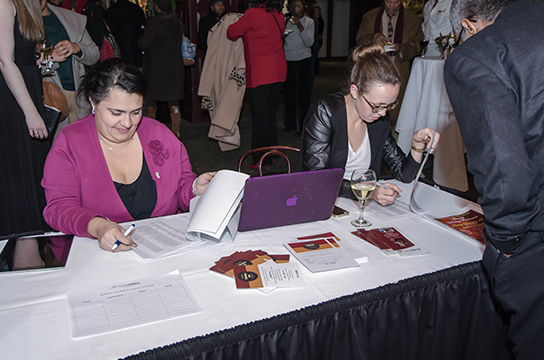 "TransAfrica volunteer and Nora Rasman check-in guests to the reception at Clyde's following the screening of ""Mandela: Long Walk to Freedom"""