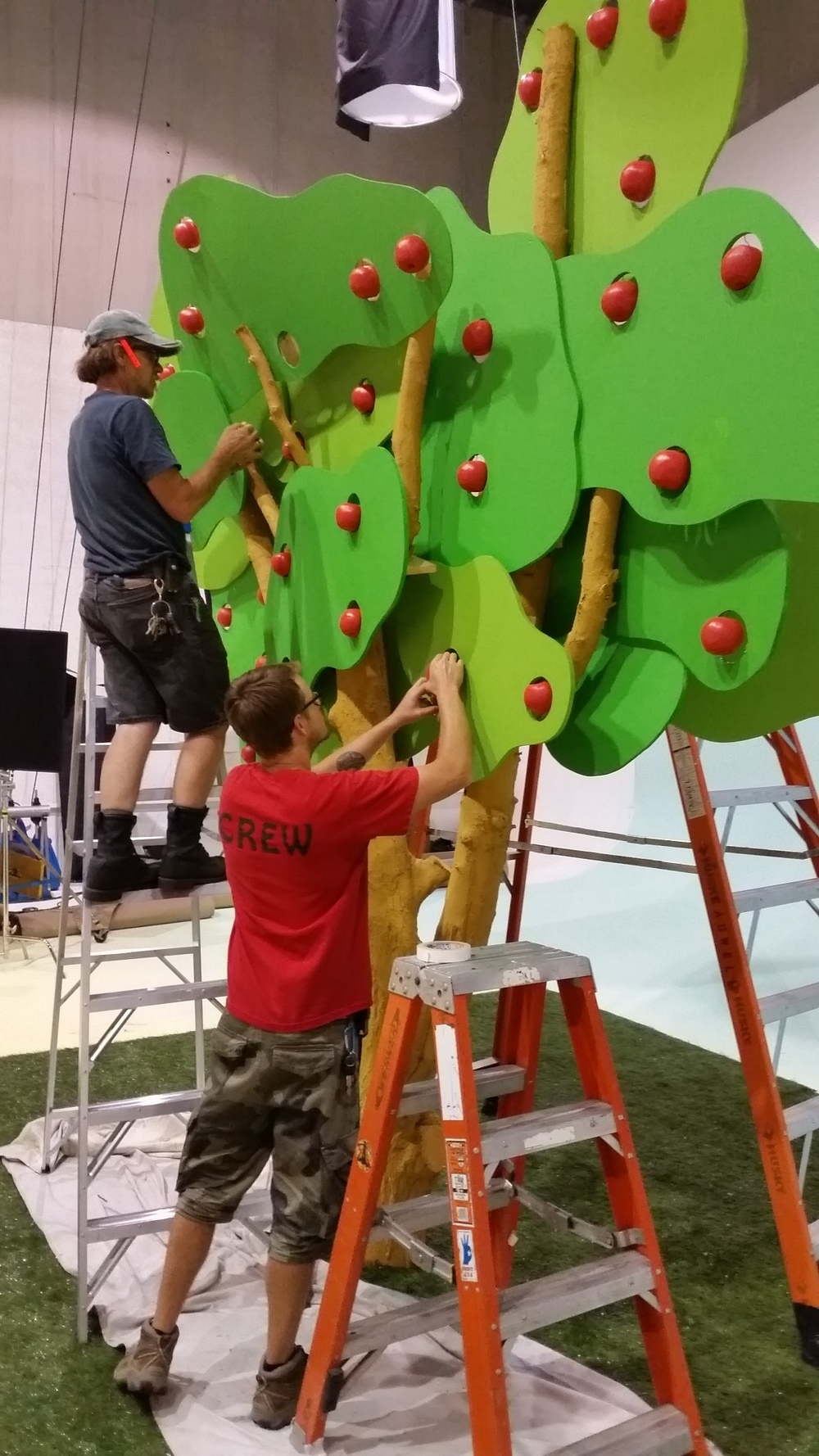 Union Set Dresser gary Surber (on ladder) works on a set piece for Health Partners with art assist tom kristjanson.