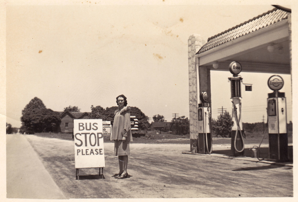 George Frances Wilson at bus stop in from of Esso Station operated by her husband.  Photo courtesy of Kay Wilson Lydon.