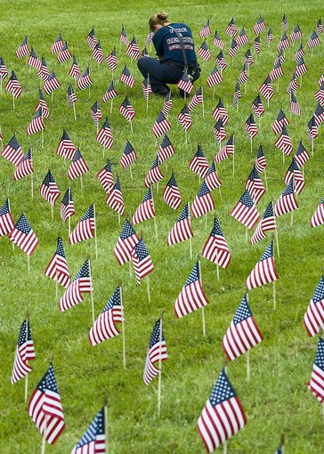 A firefighter repairs one of 3000 flags placed in a lawn in Maryland to honor those that died in the attack on 9/11 back in 2001.