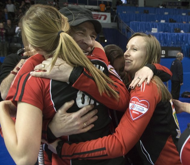 Earle embraces the team after winning their first Scotties title. - CP Photo