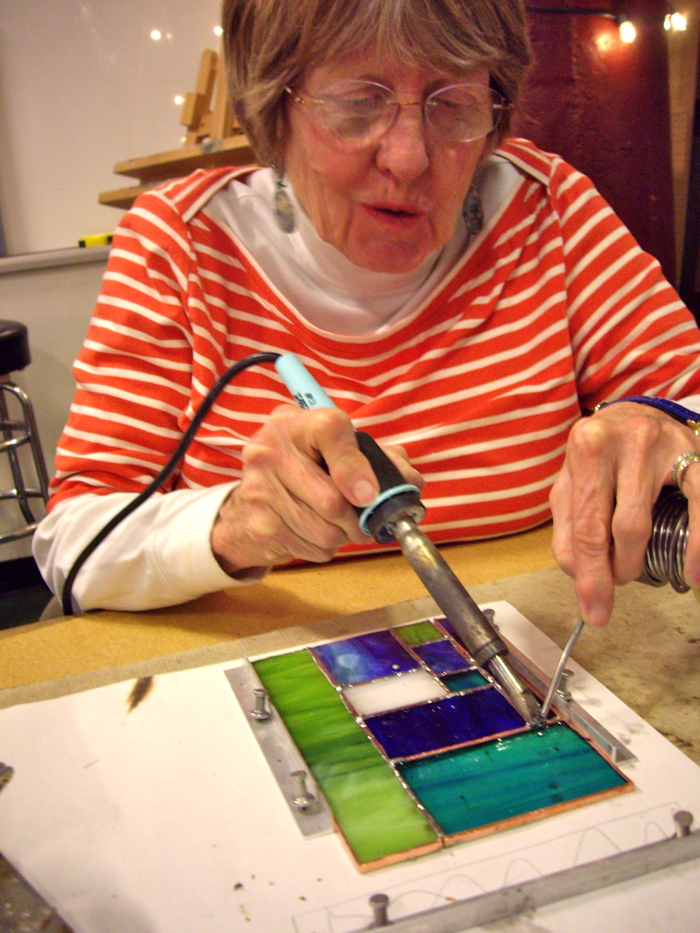 Candace runs a solder bead down her stained glass piece.