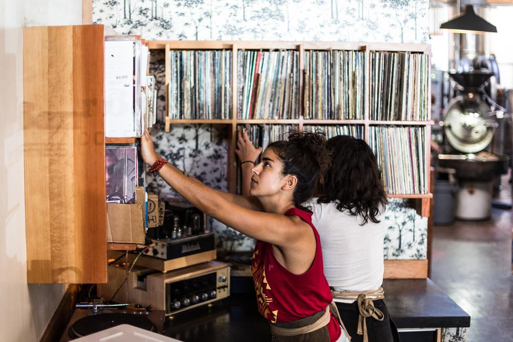 A barista sorts through the cafe's rich vinyl collection.