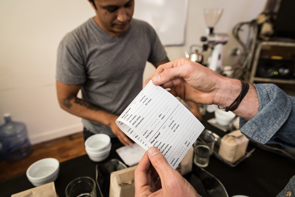 Baristas learn how beans are graded based on a set of standard criteria.