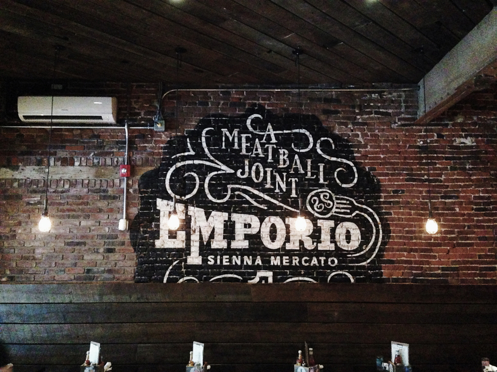 "The Emporio seal painted on the natural brick walls, ""ghost sign"" style"
