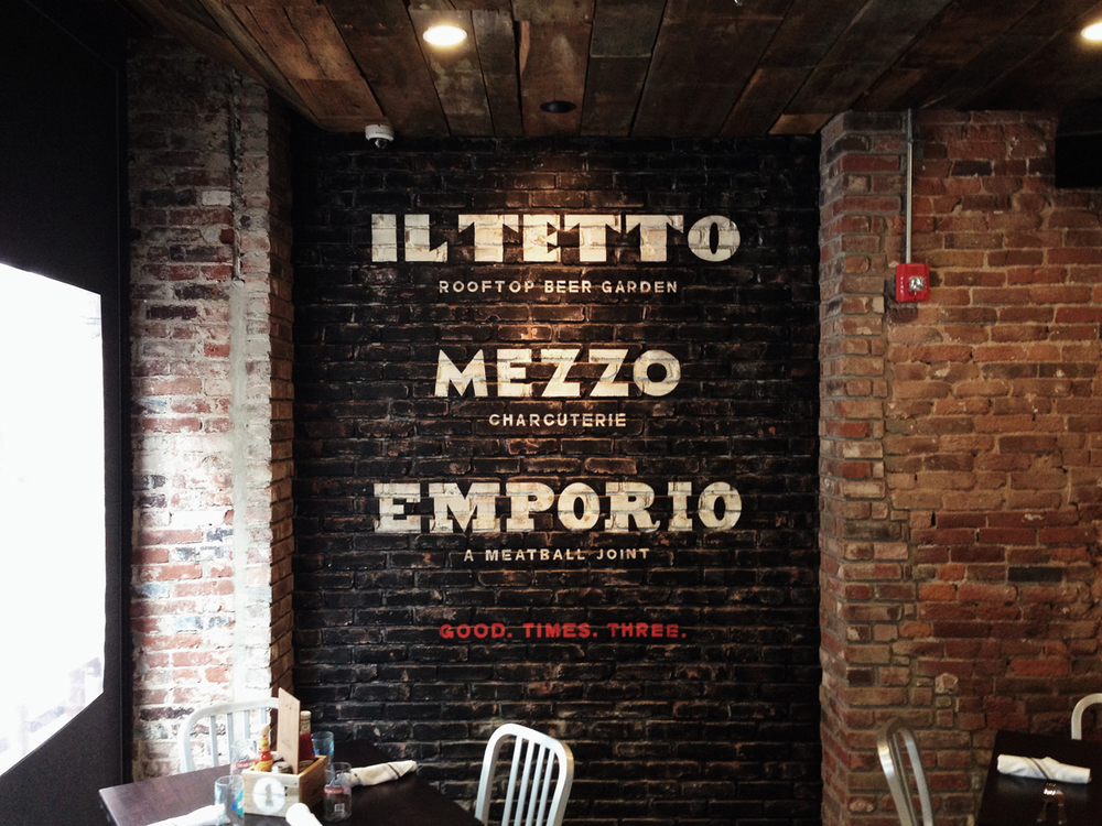 The three hand-drawn wordmarks for each unique level of the restaurant, painted on the brick wall of the heated front patio with functional garage door for the cold days