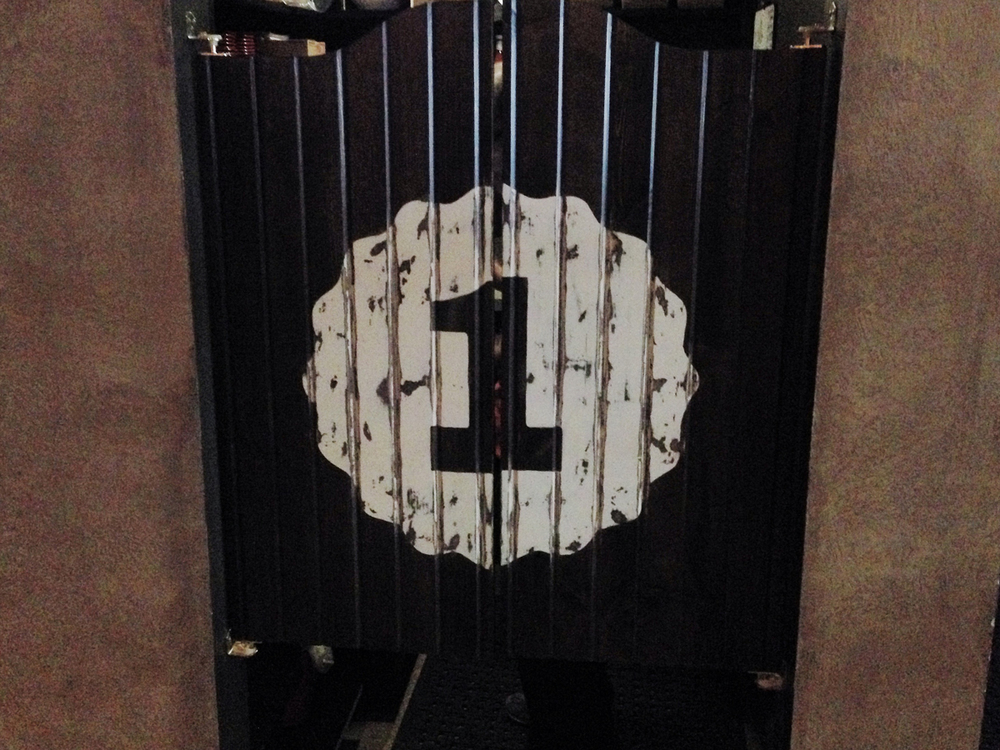 Custom hand-drawn numeral painted on the saloon-style swinging doors that hide the server area