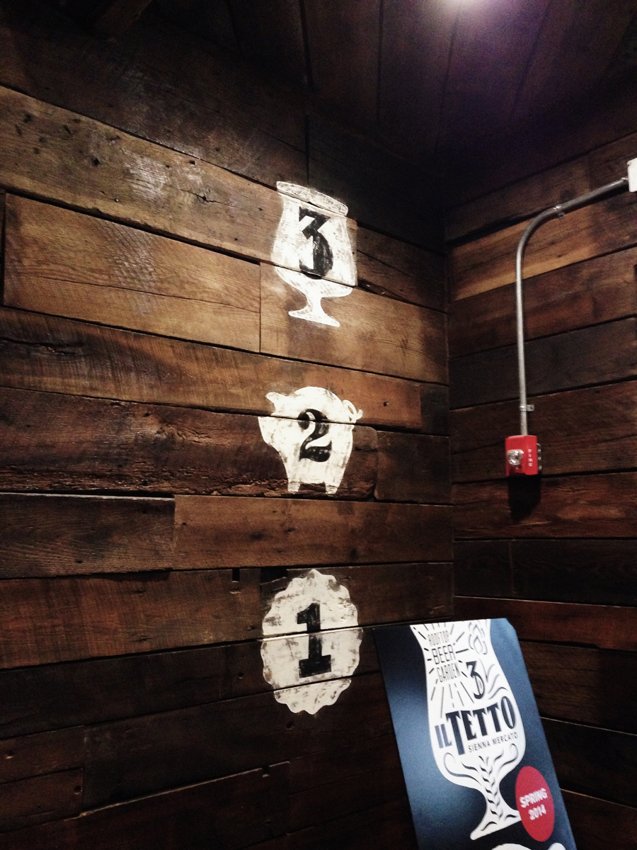 The three custom hand-drawn numerals representing each unique floor of the restaurant painted in front of the staircase to the second-floor charcuterie Mezzo