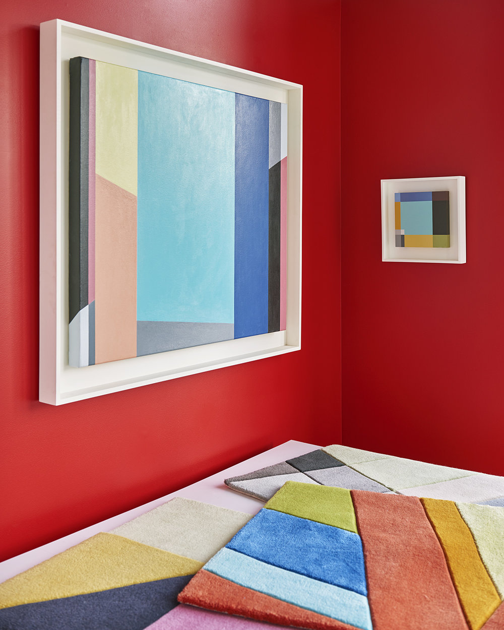 the paintings sing on the red-walled solarium.  on the left, MUSICOLOGY, oil on canvas, 24x27 inches, 2011; on the right, PLAID, oil on panel,  8x8 inches, 2008. On the flat file are samples of each of the rugs, with cut pile and pencil carving.