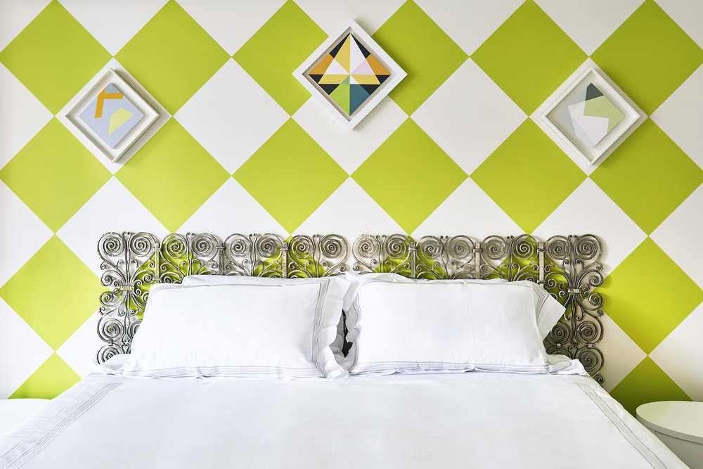 Allan designed the wrought stainless steel headboard, which juxtaposes well against the apple green checkerboard.  Periodically, we hang paintings at an angle to go with the flow.
