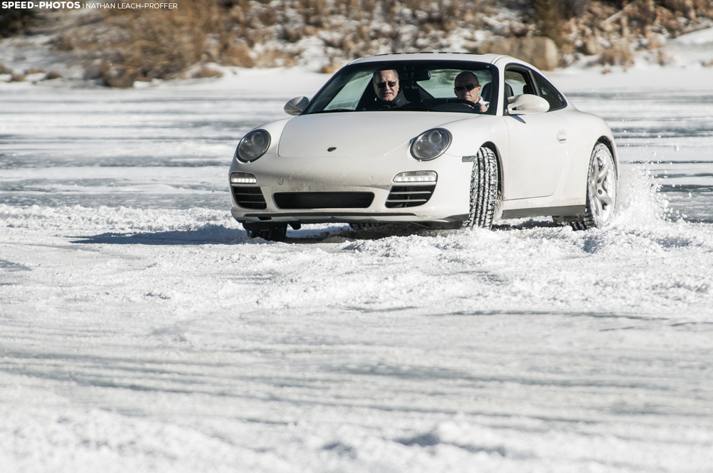 Porsche 911 drifting on a frozen lake covered in snow.