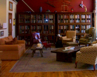 Photo of a grouping of chairs and sofas with cases of books behind them.