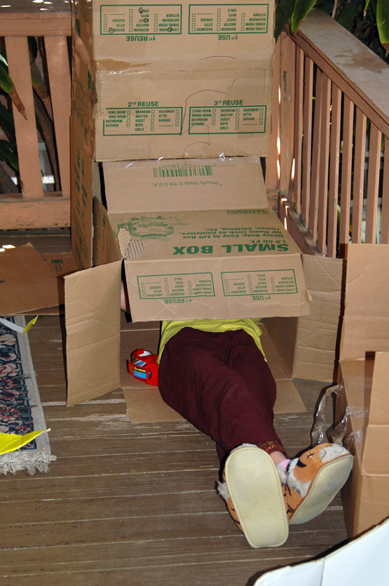 Photo of a little girl lying on a porch, with her ankles crossed, and the top half of her body inside a tower of boxes she's taping into a magnificent structure.