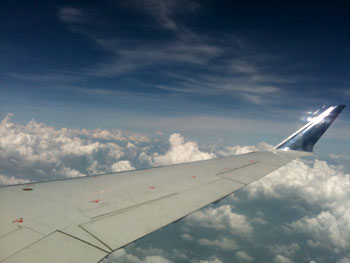 Photo shot from an airplane window; pretty clouds and a wing!