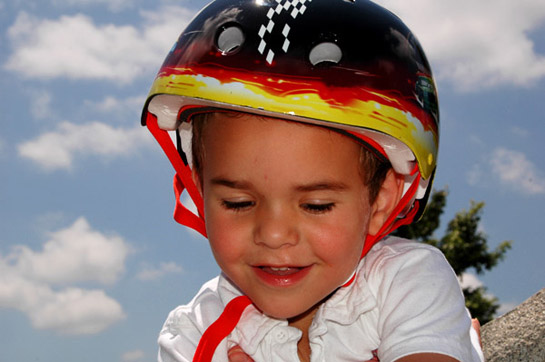 Picture of 4 year old nephew, Rami, in his bicycle helmet, gorgeous sky in background, grinning at having climbed a pile of rocks.