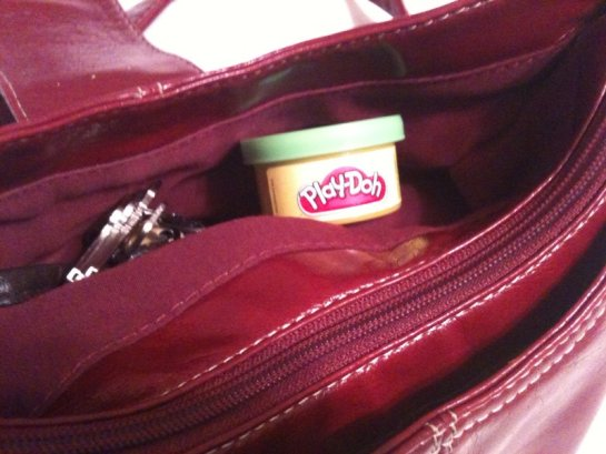 Red handbag with little tub of Play-Doh in a side pocket