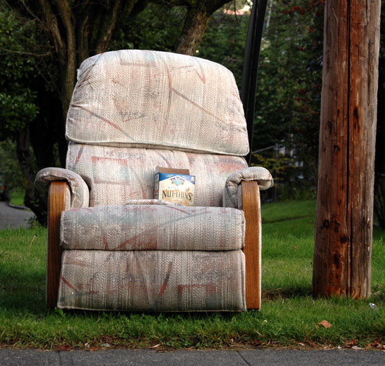 Photo of an old recliner sitting in a yard in Seattle, with a box of Nut Thins in the seat.