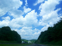 Photo of a highway on a gorgeous day with poofy clouds in a blue sky.