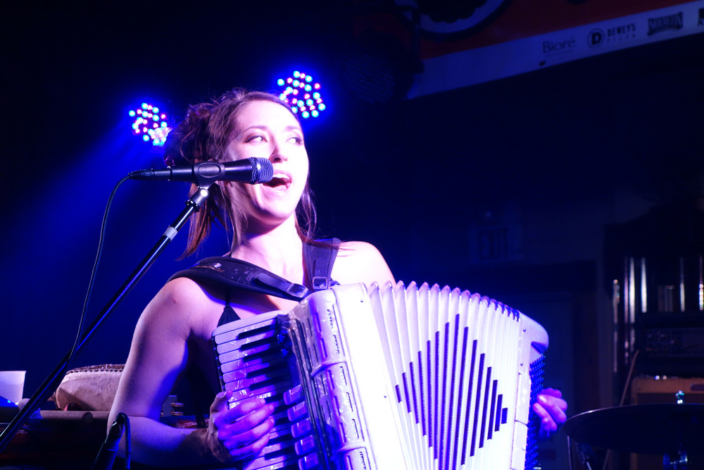 Crystal Bright playing the accordion and singing in a live performance. Photo by Mike Korach