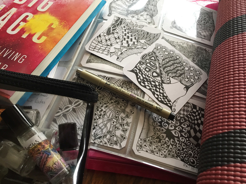 Big Magic, essential oil blends in roller balls, some of my Zentangle tiles (finished AND incomplete ones,) and one of my yoga mats.