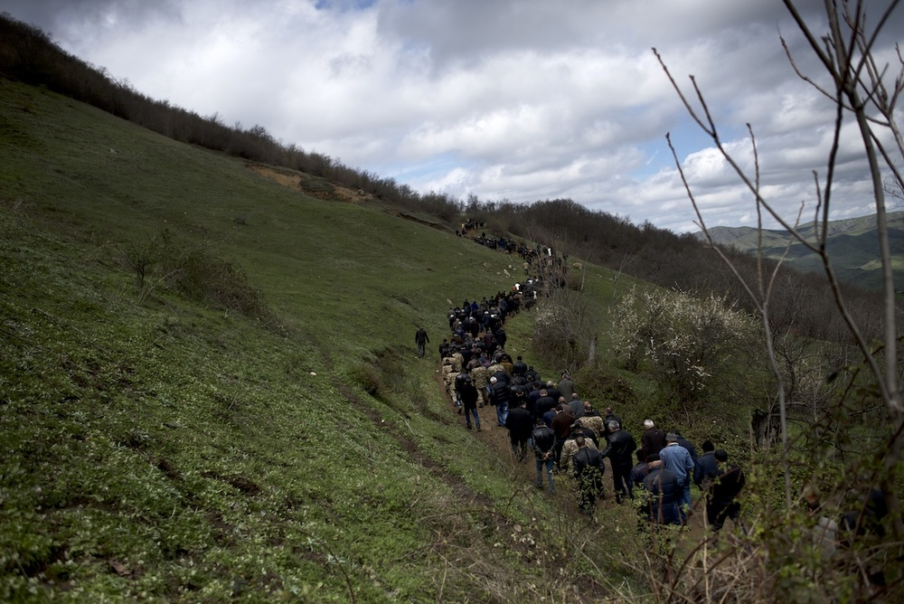 People walk up a mountain in Herher village during the burial ceremony of Vagharshak Grigoryan,12, who was one of the four civilians killed as a result of the re-ignited conflict between April 1 and April 5.