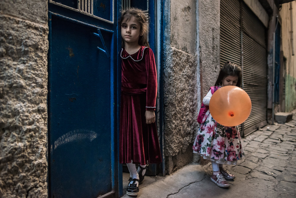 Ilknur, 6, and Berçem, 2, play in one of the numerous backstreets of Sur, preparing for a family gathering.