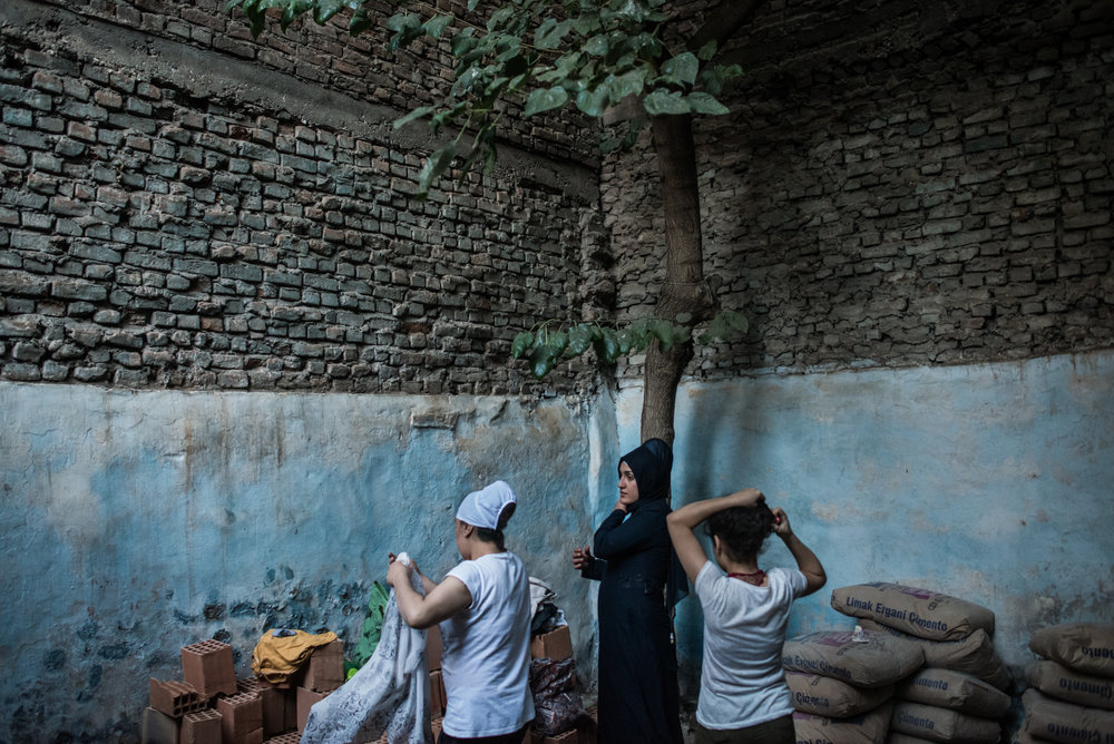 A family returns home after the clashes between Kurdish extremists and and Turkish police calm down. As they reconstruct their old homes, they often have to dress outside.