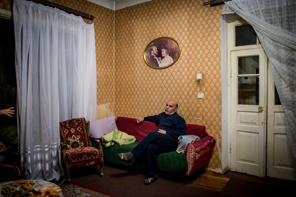 Khachig Manuel, 56,  in the living room of his family's rented house in Yerevan. Khachig's engagement photo from 1993 hangs on the wall, and is the only item his family has as a memory from Syria. Khachig has problems with his heart, and stays silent while his wife Mari tells the story of the bureaucratic hardship she was going through to arrange his free healthcare.