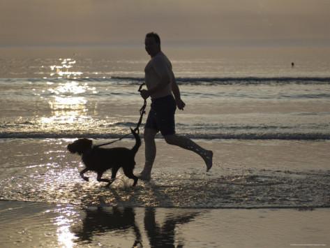 brimberg-coulson-silhouette-of-man-running-with-dog-on-beach-sunset-romo-denmark.jpg