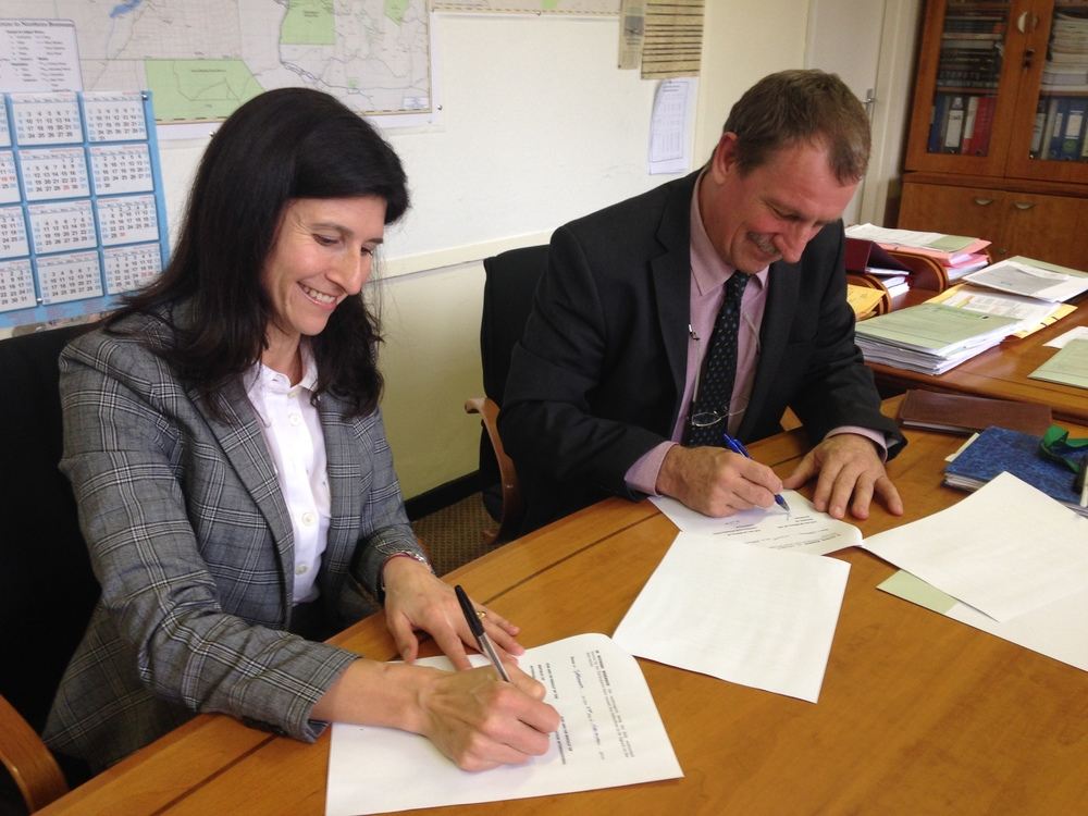 Daniela Raik, Ph.D., Vice President, Field Program Management for Conservation International (left) and the Permanent Secretary of the Ministry of Environment, Wildlife and Tourism, Mr. Neil Fitt, who signed on behalf of the government of Botswana, sign the updated Memorandum of Understanding with the Government of Botswana in the offices of the Permanent Secretary at the Ministry on December 8.