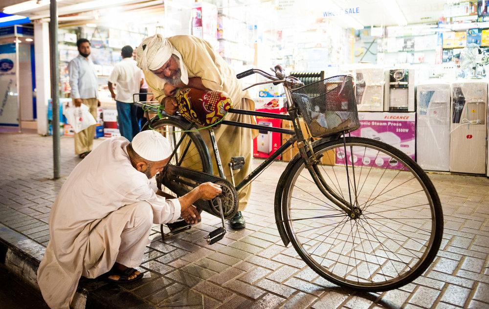 Reisfotografie-twee-mannen-met fiets-Dubai.jpg