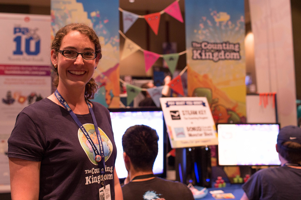 Founder Jenna Hoffstein stands in front of The Counting Kingdom table at PAX Prime 2014