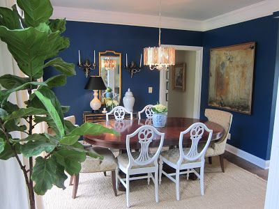 A rich, vivid cobalt blue in this dining room allows the art, lighting and gold accessories to stand out and make a statement.