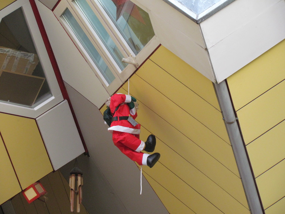 Santa climbing into one of the houses