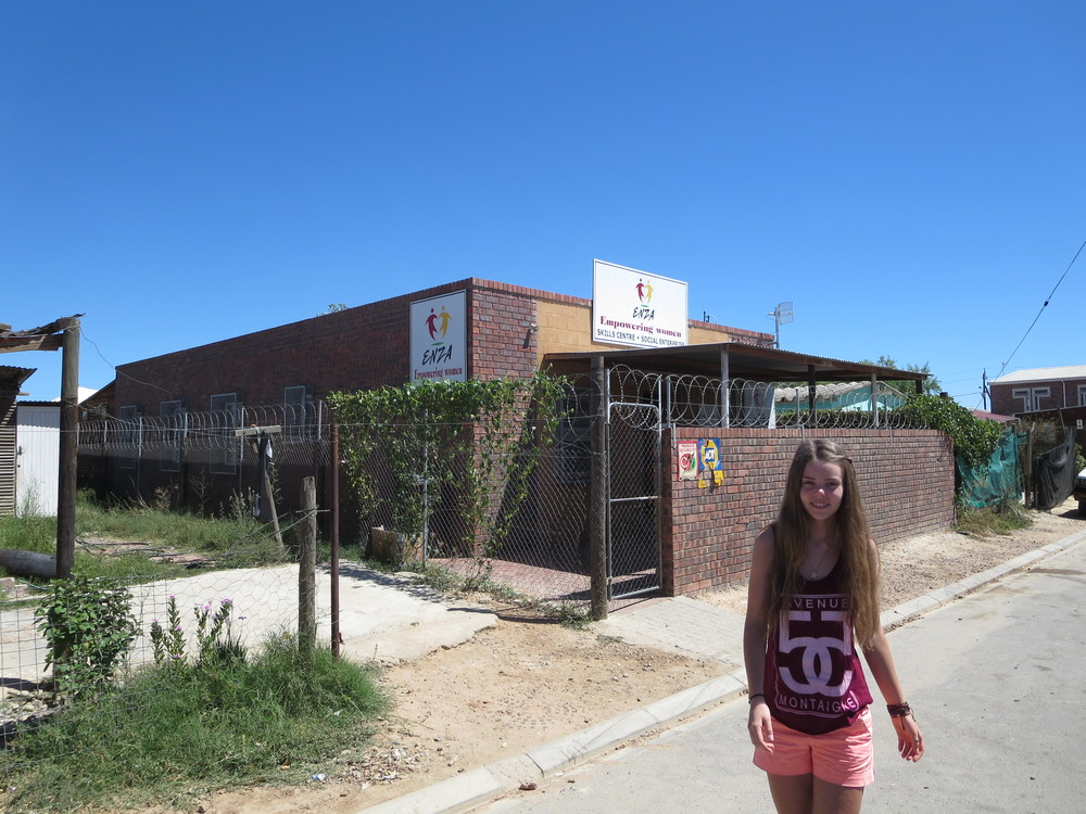 Dora in front of Enza in the middle of one of the Townships. Enza: empowering women.  An initiative that changes lives.