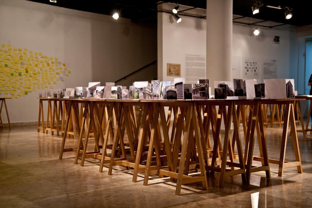 Vista geral das mesas expositivas | à esquerda, mural de Post-it aberto à intervenção do público