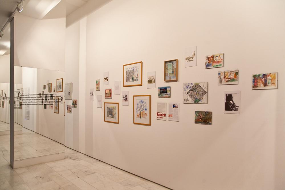 Na parede, uma nuvem de pinturas, poemas e fotos de Hygina aproxima o público do complexo universo da arquiteta