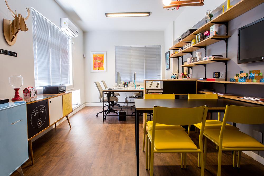 Os ambientes de trabalho e de reunião, separados pelo mobiliário, integram-se visualmente por meio da estante, que ocupa a maior parede