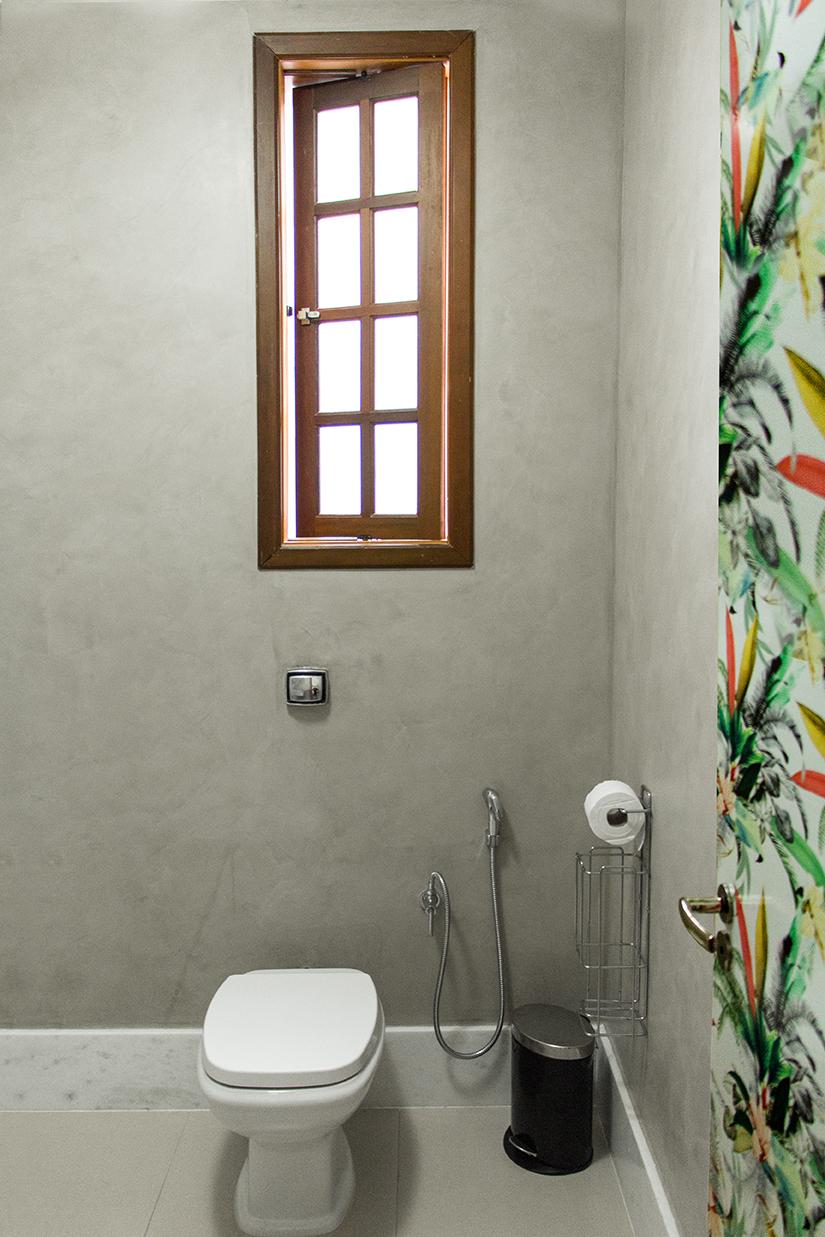 Pintura com textura de concreto nas paredes, rodapé alto de mármore, estampa adesivada na porta.