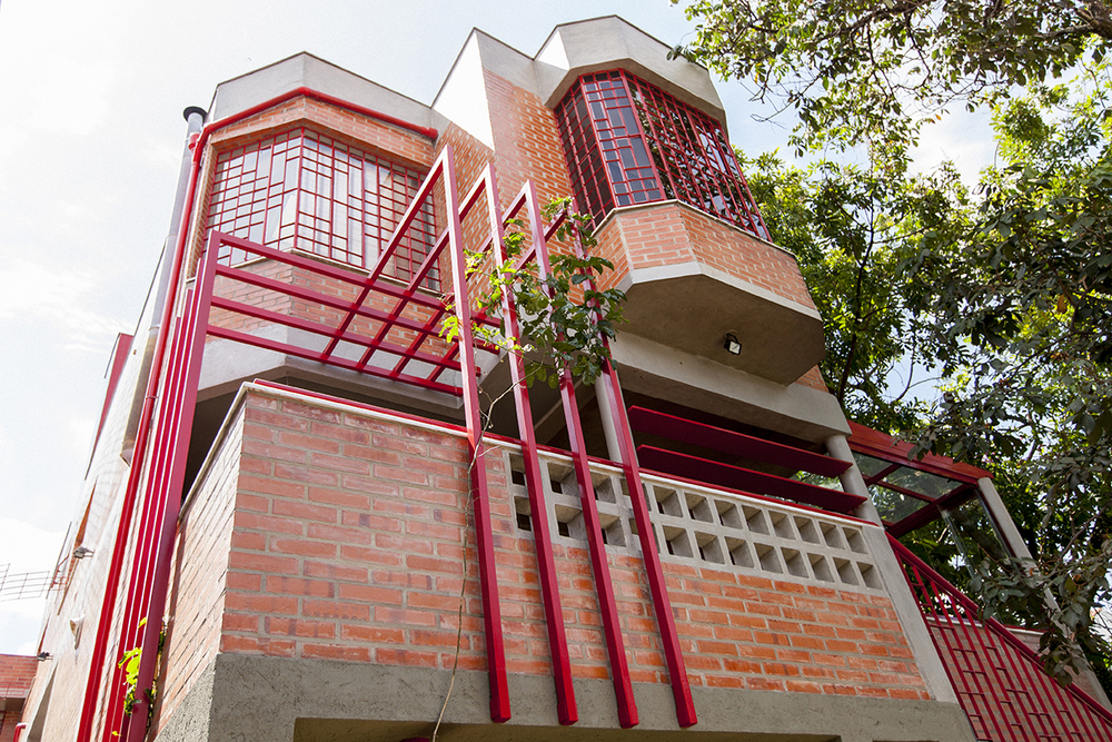 Tijolos maciços, cobogós de concreto e elementos metálicos vermelhos foram utilizados para garantir uniformidade do volume da nova varanda com o da casa.