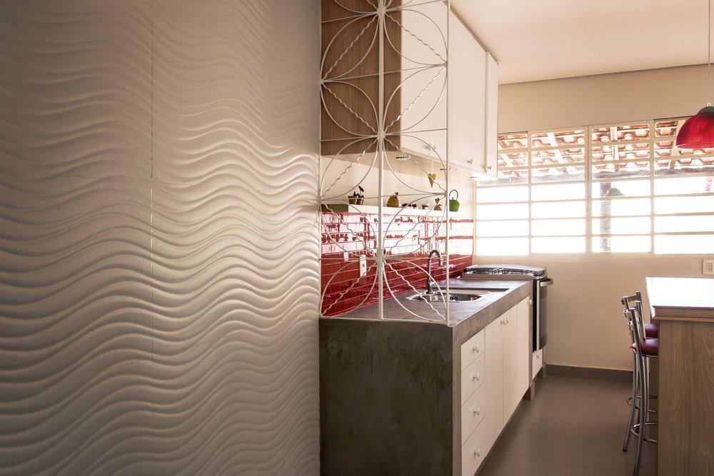 Cozinha com bancada de concreto, gradil de serralheria e parede revestida com porcelanato e pastilha.