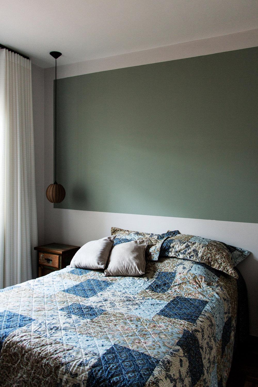 Quarto com pintura substituindo cabeceira da cama.