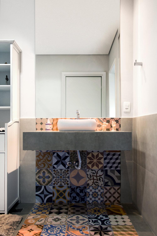 Banheiro com faixa de ladrilhos no piso e na parede, bancada revestida com porcelanato.