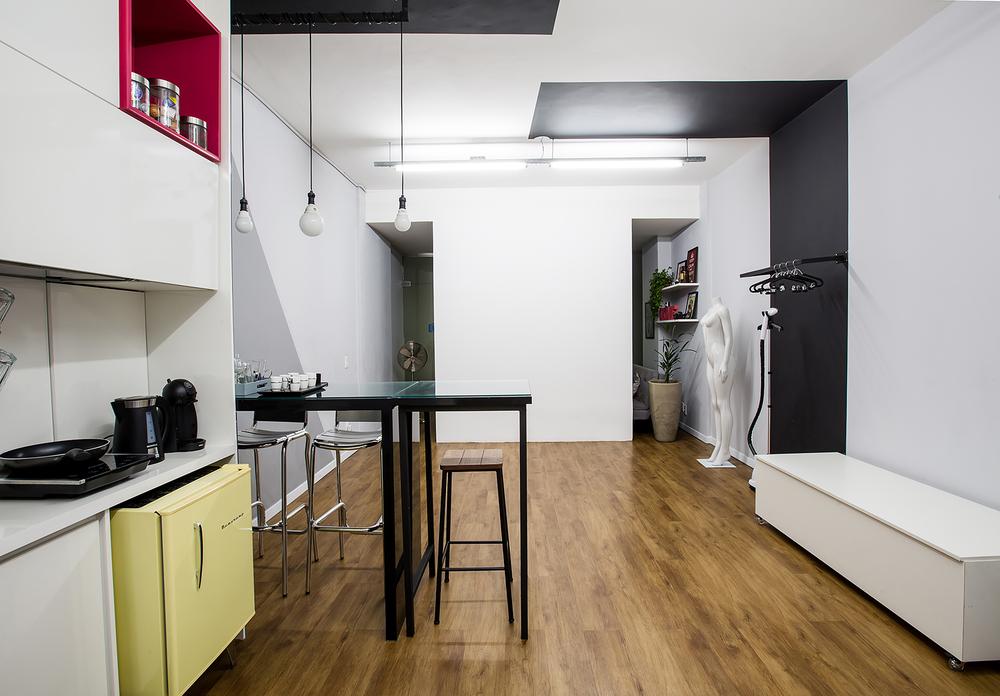 Espaço para fotos com fundo branco. Arara de metalon preta marcada com faixa de pintura na parede e teto.