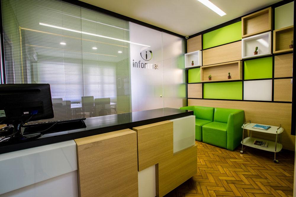 Recepção - formas geométricas como releitura do estilo do edifício, verde vibrante presente na identidade visual da empresa.