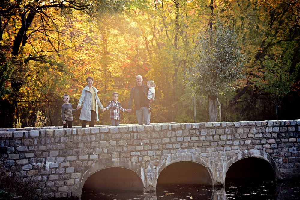 _DSC7242 family hold hands on stone bridge gorgeous warm color.jpg